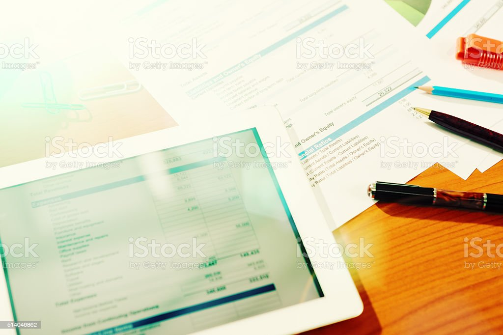 Figures and financial statements on tablet with  printouts on desk stock photo