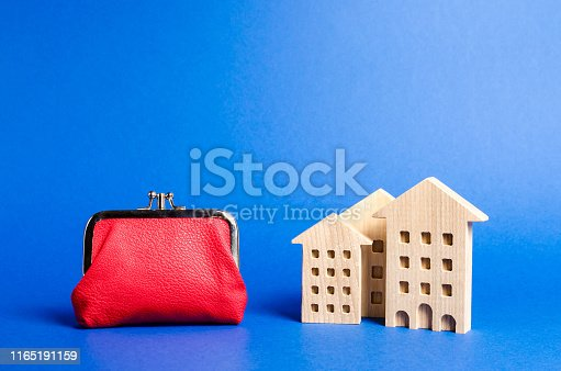istock Figures of residential buildings near a large red wallet. concept of the cost of maintaining the building and utility bills. Modernization of housing, improving energy efficiency. Saving to buy a home 1165191159