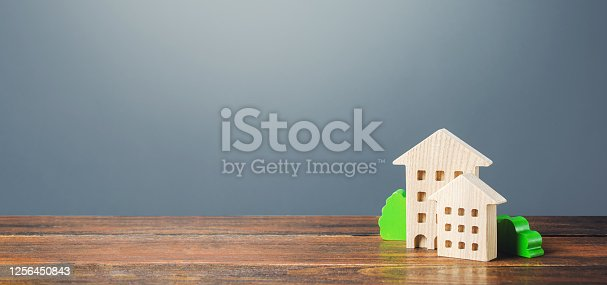 915688450 istock photo Figures of residential buildings on a gray background. Buy purchase and sale, housing rental. Community owners of apartments. Construction industry real estate, maintenance utilities. Mortgage loan 1256450843