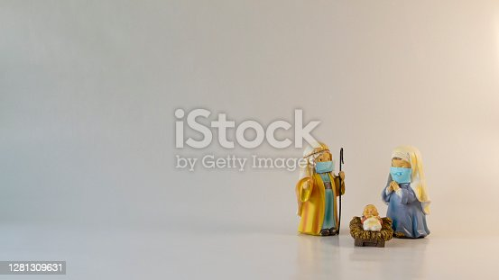 istock Figures of Saint Joseph, the Virgin Mary and the newborn baby Jesus with hygienic masks. Christmas with the Covid-19 pandemic. Copy Space 1281309631