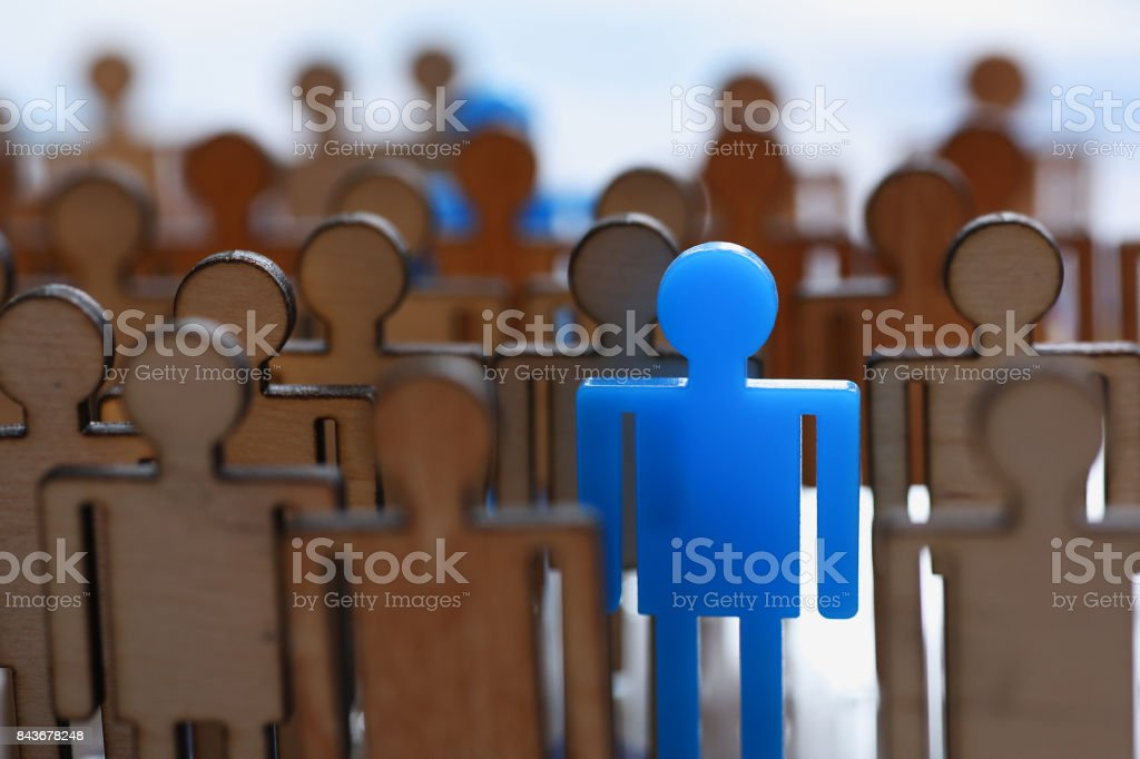 Figurine blue man in the crowd of wooden figures stock photo
