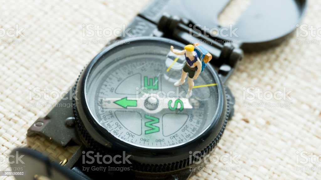 figurine model on the compass navigation guide - Royalty-free Antique Stock Photo
