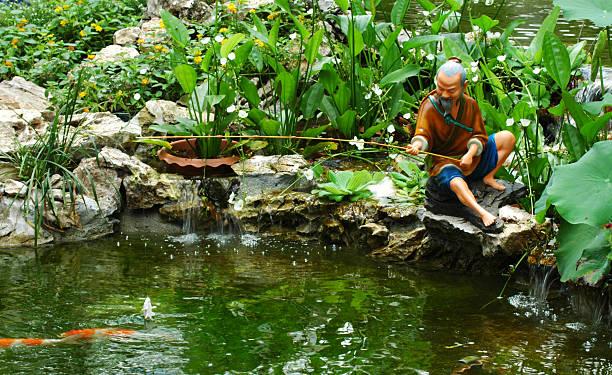 figur der chinesischen fisherman - teichfiguren stock-fotos und bilder