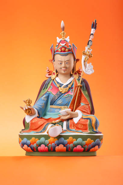 Figurine of Padmasambhava on an orange background. The clay figurine of sitting Padmasambhava - Guru Rinpoche, make in a traditional Tibetan manner, colorful painted, isolated on an orange background. bodhisattva stock pictures, royalty-free photos & images