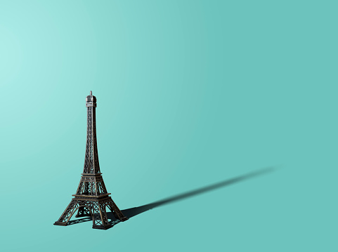 Figurine of the Eiffel Tower on a pastel background.