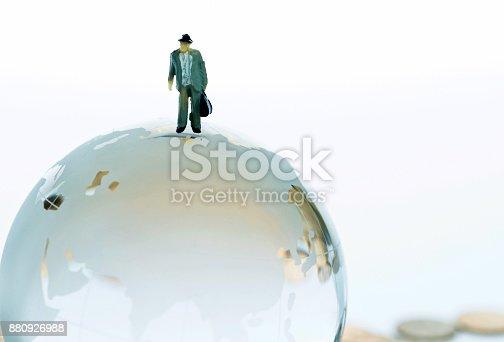istock Figurine on top of globe 880926988