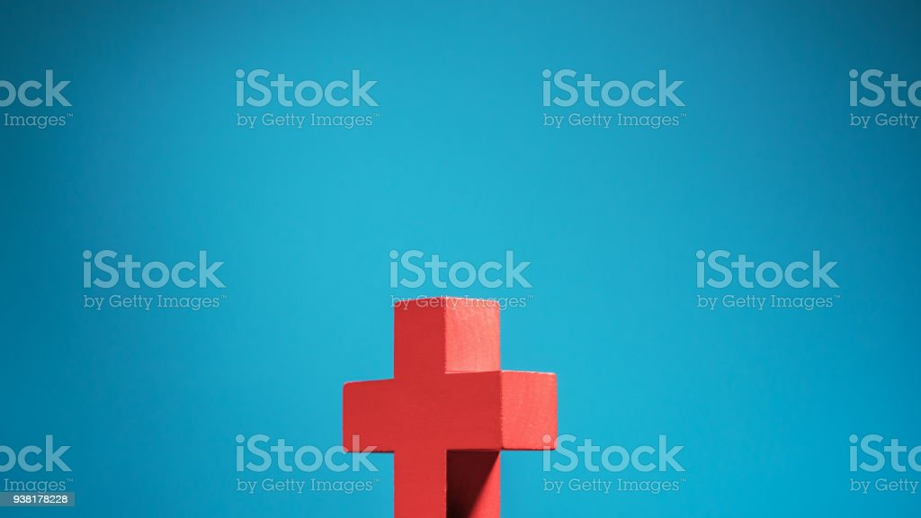 Figurine wooden cross on  blue background with copy space. stock photo