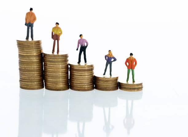 figurines standing on stack of coins - figurine stock photos and pictures