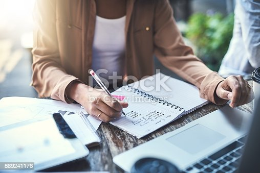 Closeup shot of an unrecognisable businesswoman writing notes at a coffee shop