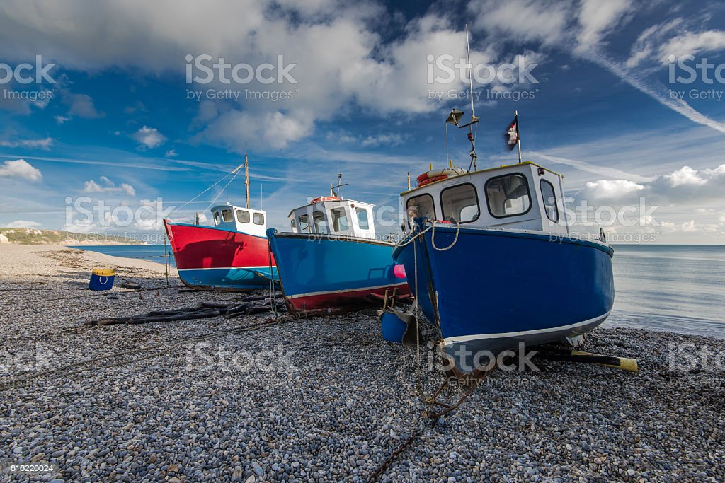 Fiherman boats on pebles at beach in Beer, Devon,UK stock photo