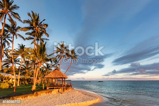 Beautiful sunset over a typical Fijian beach hut surrounded by palm trees at the coral coast beach in the south of Viti Levu, Fiji Island, Melanesia, Oceania.