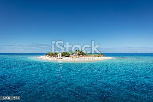 Beautiful small island in the middle of the south pacific ocean with beach huts, lounge chairs, palm trees, surrounded with beautiful clear turquoise water. Islet, Mamanuca Islands, Fiji, Melanesia