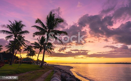 Pink sky during a colourful sunset over palm trees and beach in Fiji
