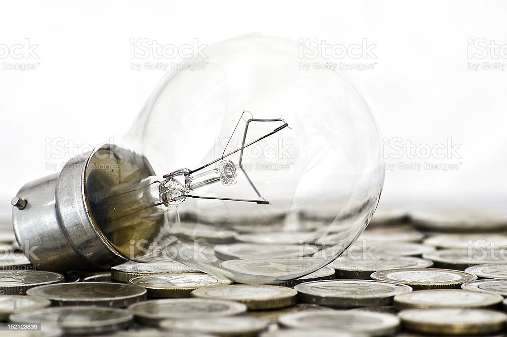 filament bulb lying on euro coins stock photo