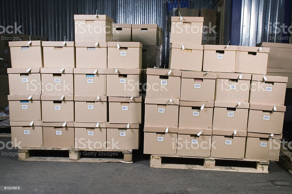 File boxes with barcodes stacked on pallet in a warehouse  stock photo