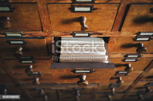 Open old style wooden drawer with index cards.
