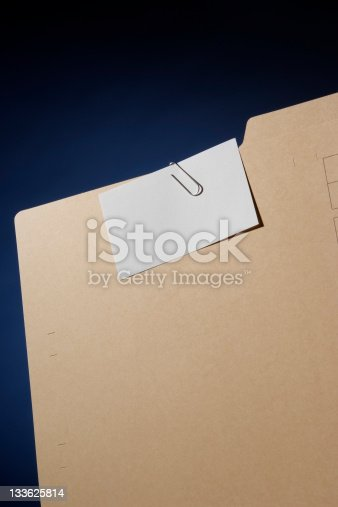 istock File folder with blank note pad against dark blue background 133625814