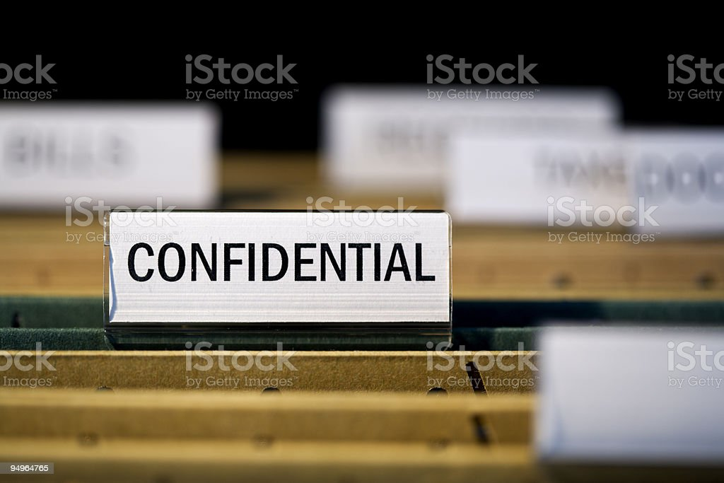 file folder with 'confidential label in filing cabinet stock photo