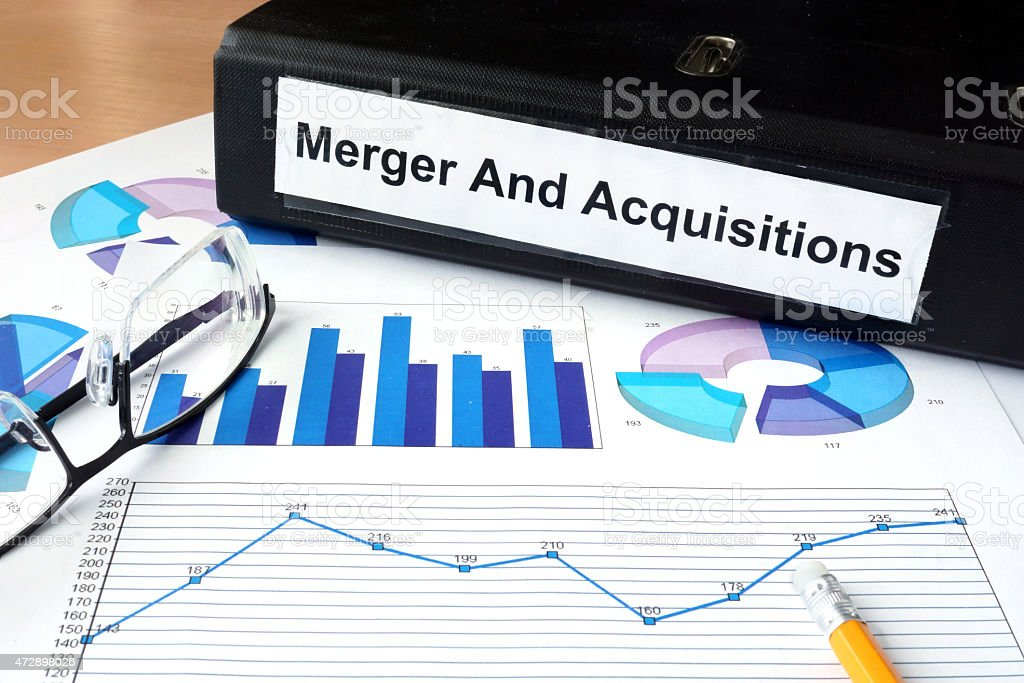 File folder with Merger and Acquisition and financial graphs. stock photo