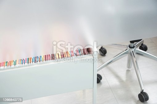 File folders in drawer partly visible under metal cubicle wall