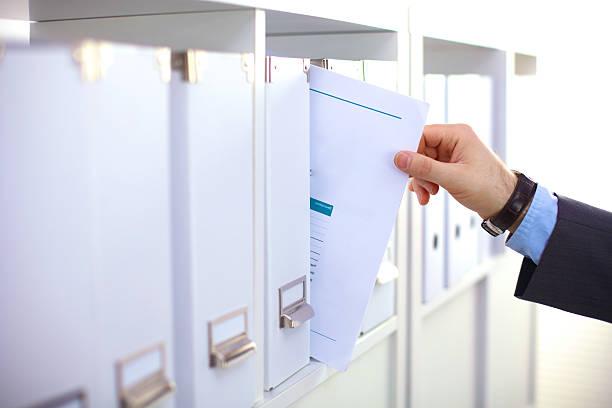 Plik folderów, stojący na półkach w tle – zdjęcie