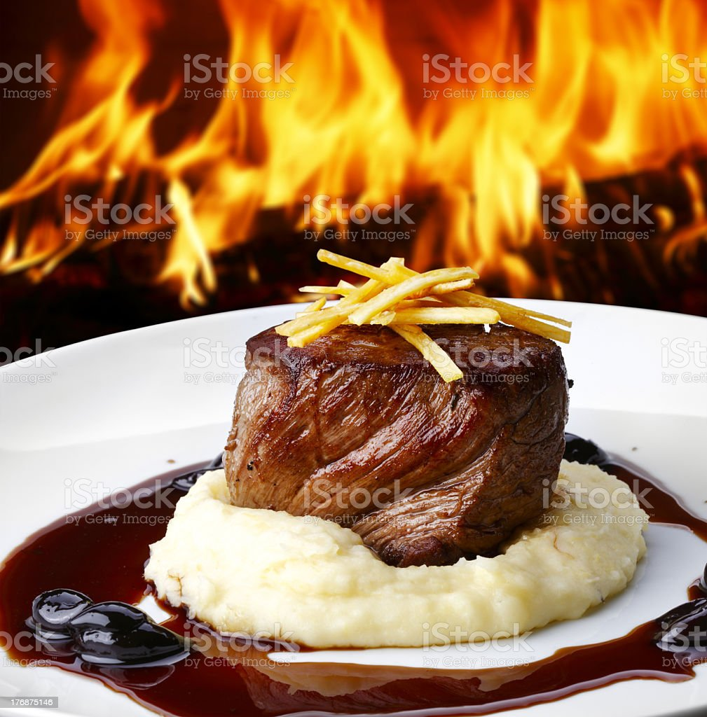 File Mignon steak dish on white plate against yellow flame stock photo