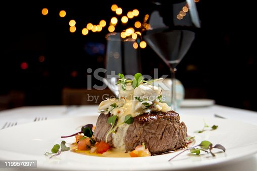 Dish of filet mignon and vegetables with glass of red wine