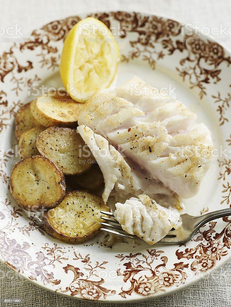 Filet of Cod with pan roasted potatoes royaltyfri bildbanksbilder