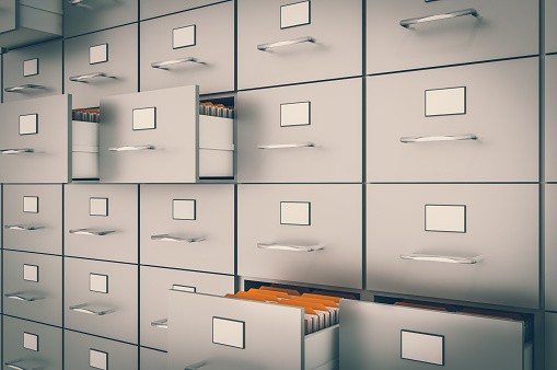 Filing cabinet with yellow folders in an open drawers