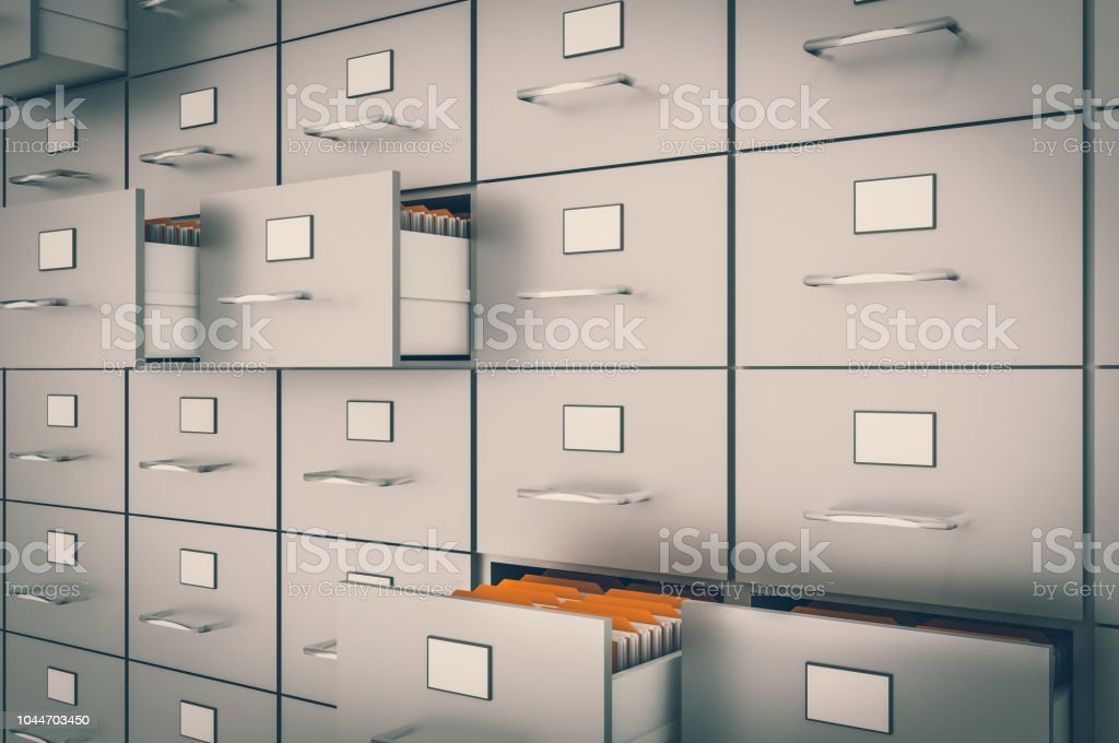Filing cabinet with yellow folders in an open drawers stock photo