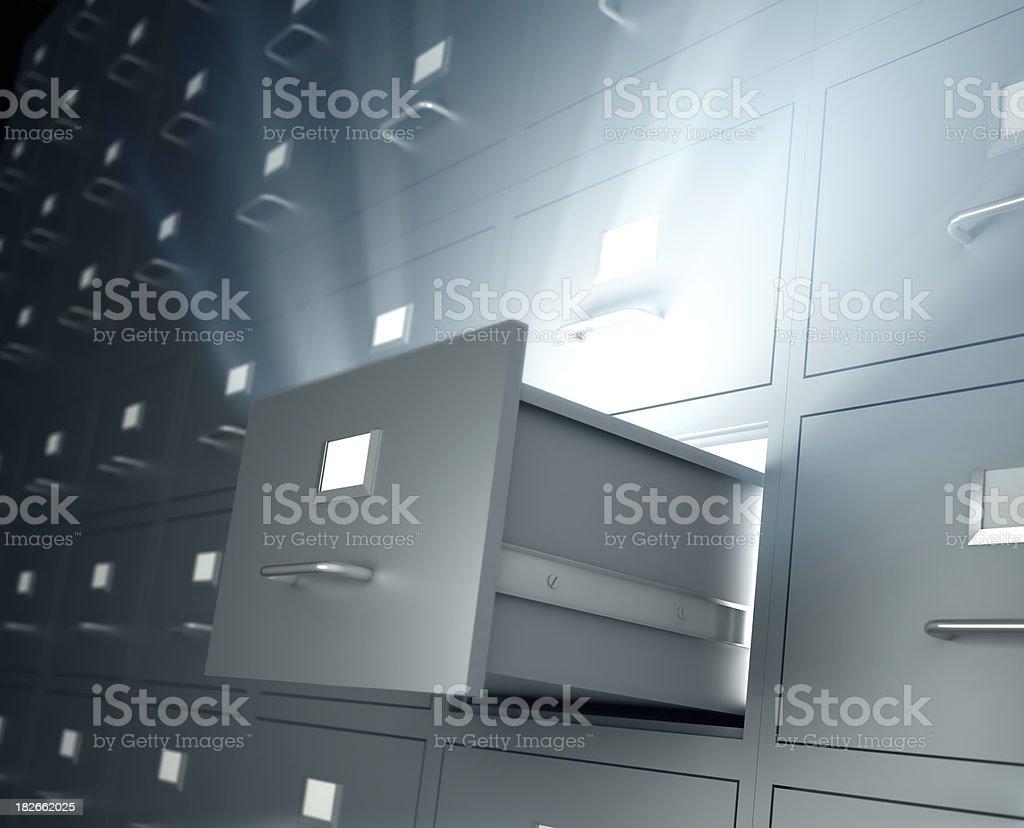 Filing cabinets, one open drawer emitting light stock photo