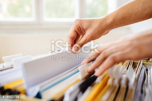 Close-up of hands searching in a file cabinet