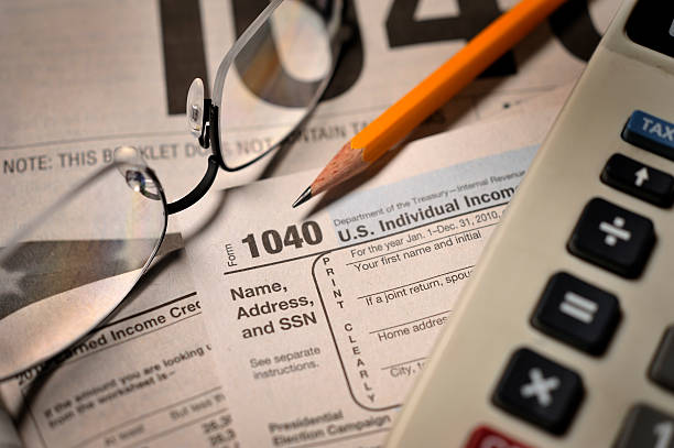 Filing taxes on IRS Form 1040 close-up view Accountant's view of filing annual taxes; selective focus on numerals