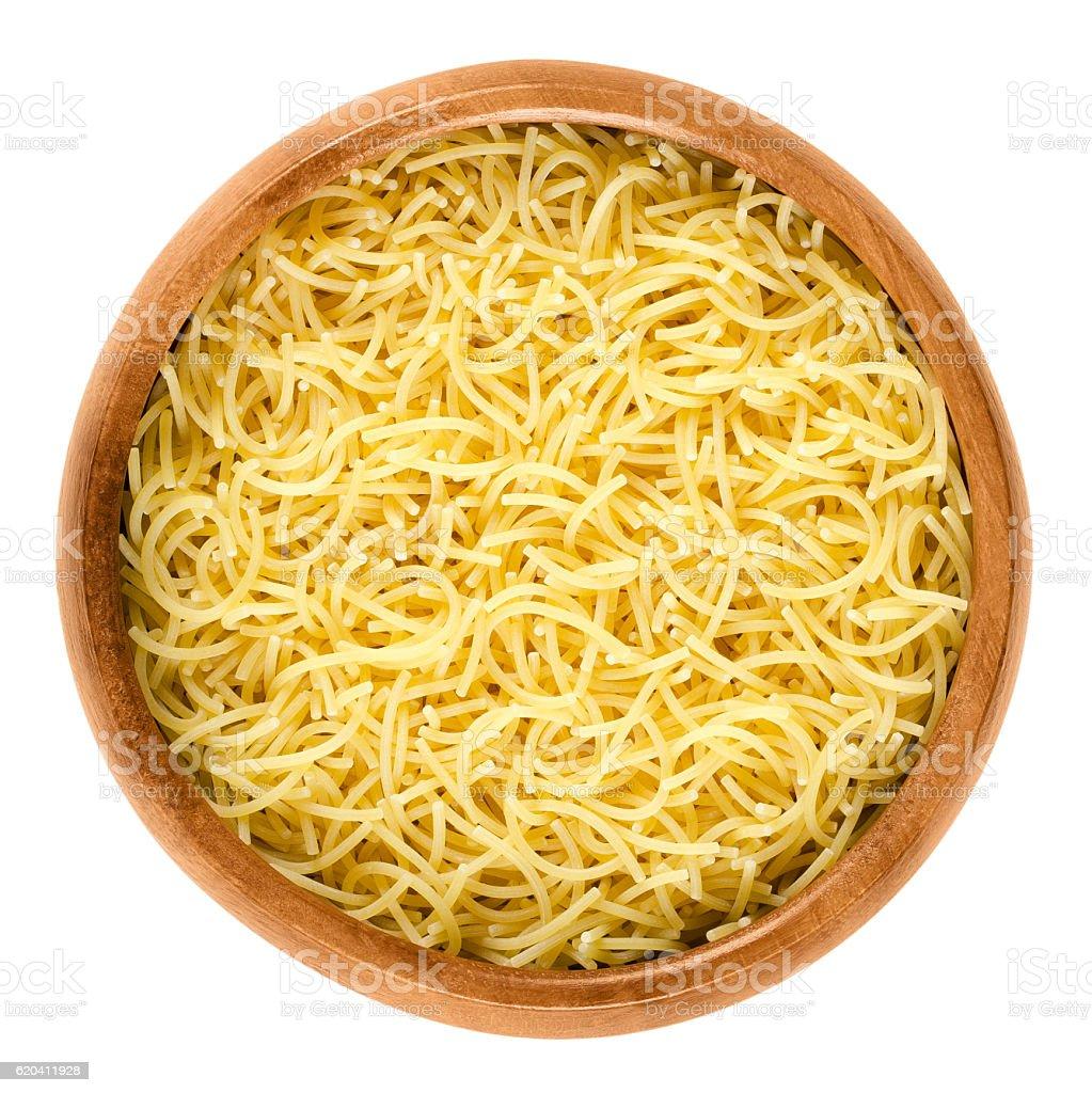 Filini short cut pasta in wooden bowl over white stock photo