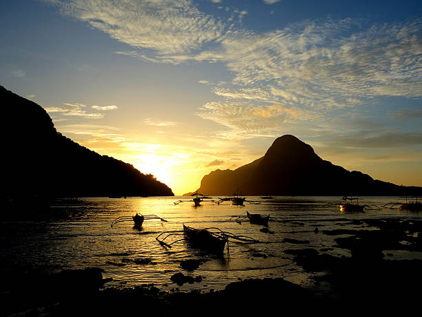 Filipino boats at sunset El Nido, Palawan Philippines Local Filipino fishing boats at sunset in El Nido bay, Palawan Philippines pinagbuyutan island stock pictures, royalty-free photos & images