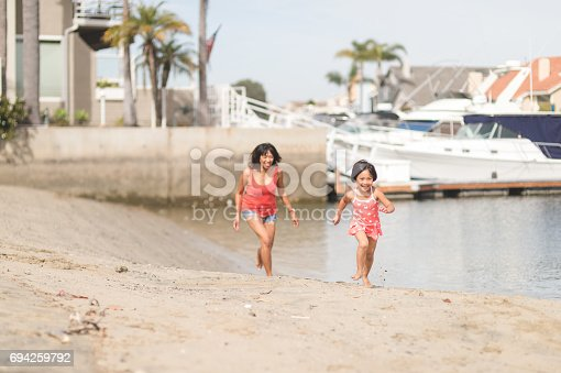 Filipino mom chasing her daughter playfully across the sandy beach