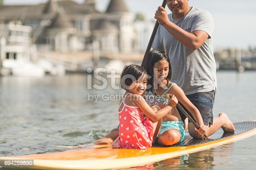 Filipino dad paddleboarding with his two daughters