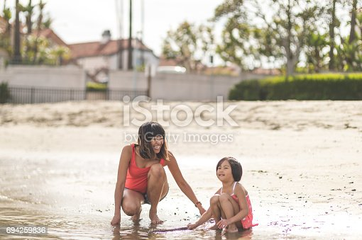 Beautiful Filipino woman playing with her daughter on the seashore
