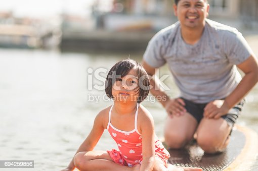 Filipino dad paddleboarding with his daughter