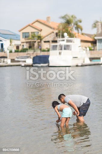 Filipino looking for fisn in the river with his young daughter