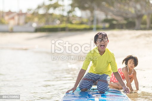 Two cute Filipino kids paddleboarding and playing in shallow water