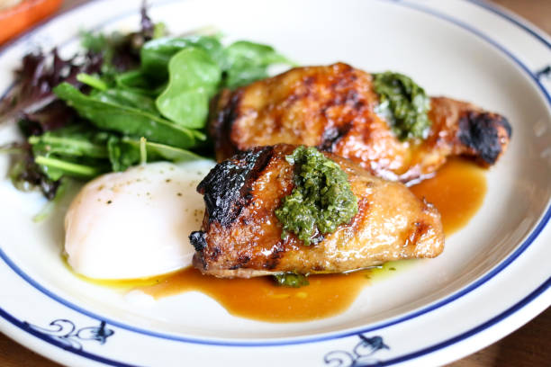 Filipino grilled chicken adobo with a poached egg and spinach salad stock photo