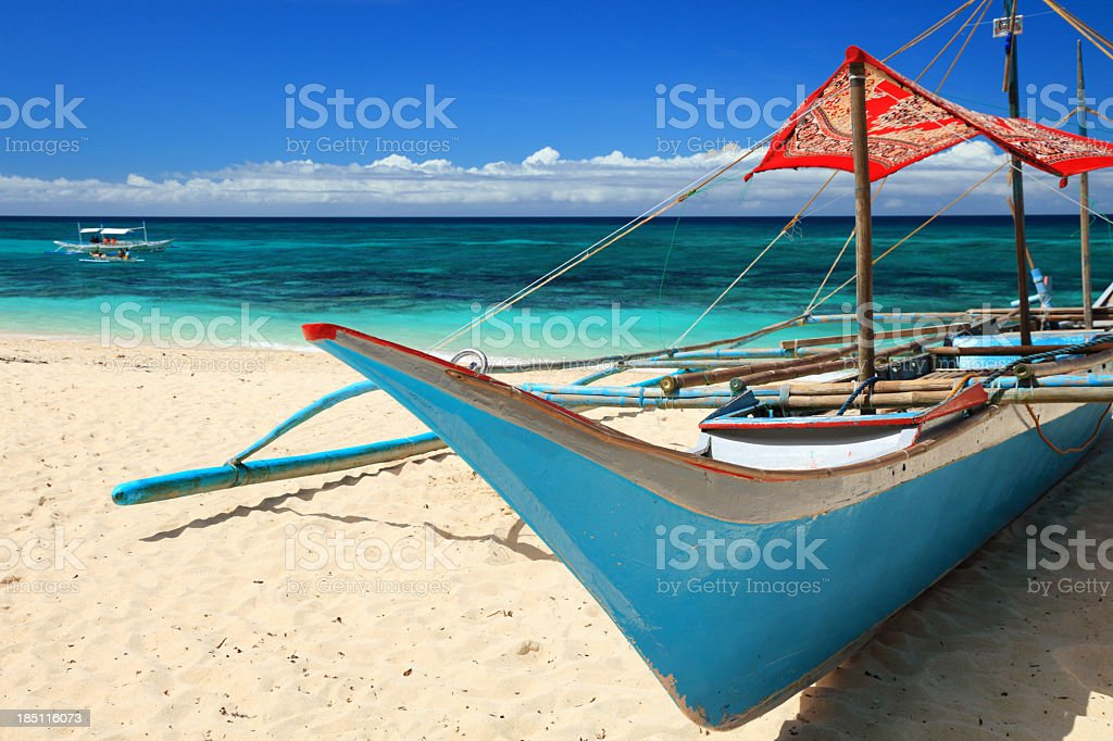 Filipino outrigger boat stranded on beach royalty-free stock photo