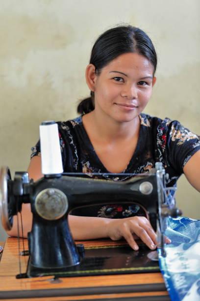 philippinische schneiderin mit einem vintage-modell der nähmaschine. sipalay-philippinen. 0402 - nähmaschinenschrank stock-fotos und bilder