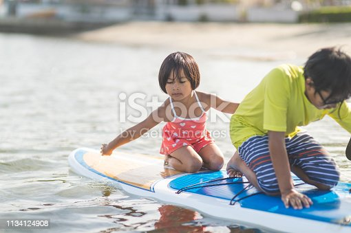 Two cute Filipino kids paddleboard in shallow water. Big brother is wearing a yellow shirt and in front while little sister is kneeling in the back and helping paddle.