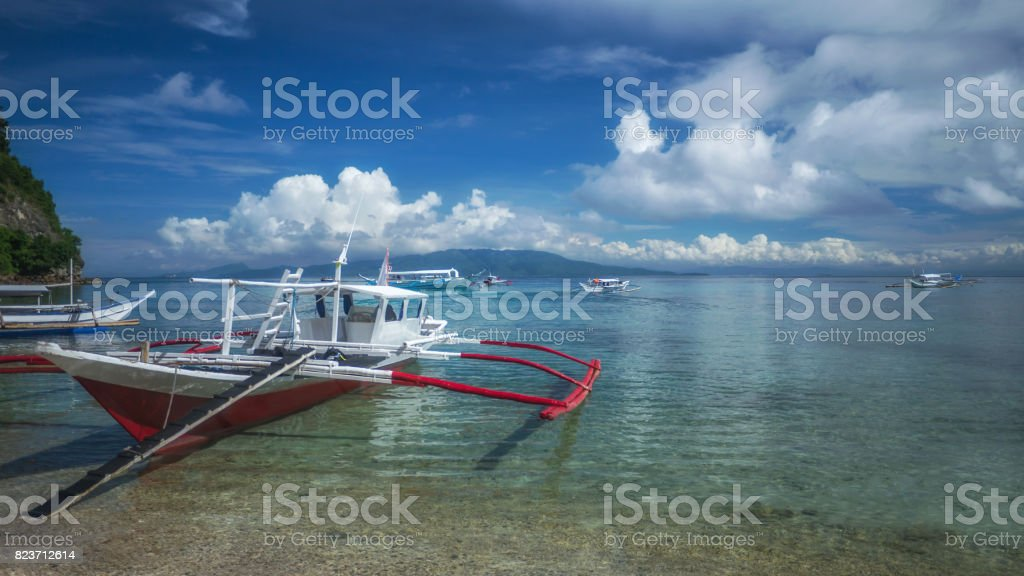 Filipino traditional wooden outrigger boats on a tropical island, Puerto Galera, Philippines. stock photo