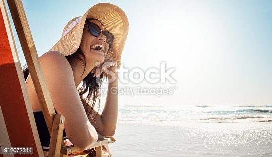 Shot of an attractive young woman relaxing on chair at the beach