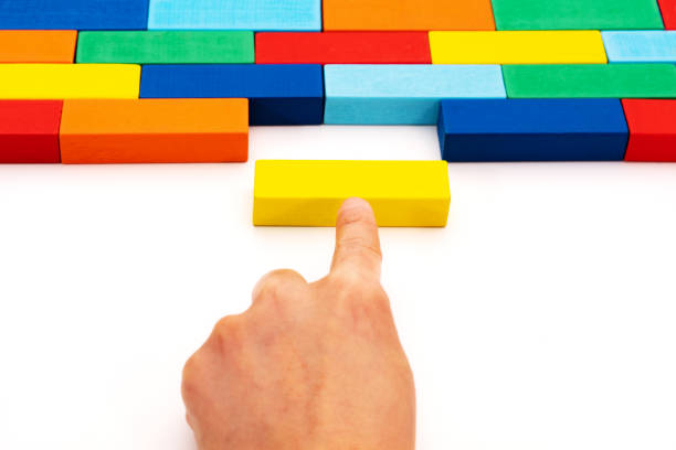 fill in business solutions concept, a piece of wooden block puzzle fit in a blank space - riempire foto e immagini stock