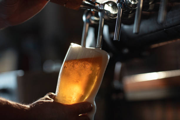 Fill it up! Fresh beer filling the glass directly from the tap.  With extra foam spilling over glass. beer glass stock pictures, royalty-free photos & images