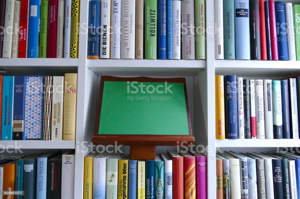 Filled books shelf close up with a green empty paper: space for copy stock photo